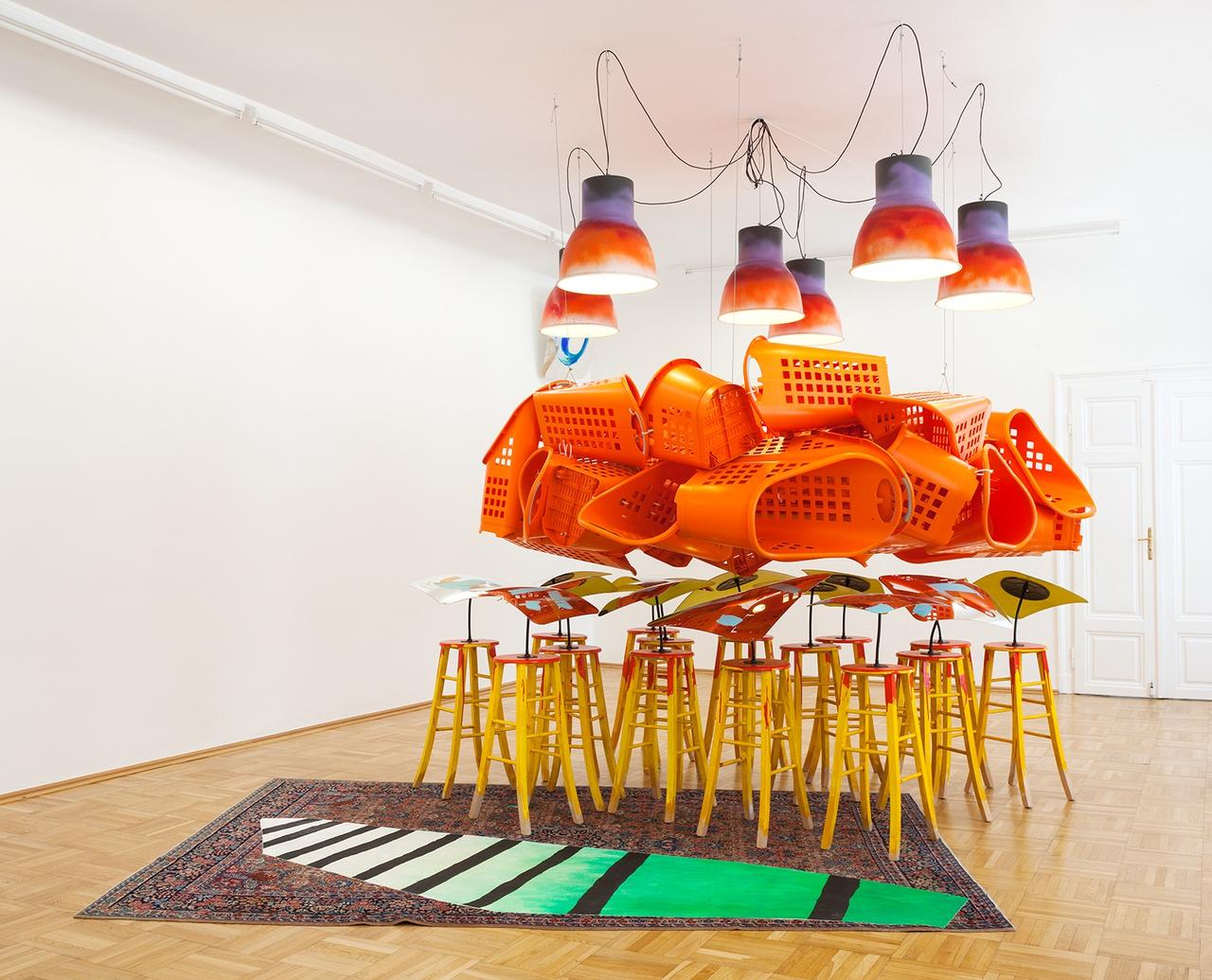 Een felgekleurde kunstinstallatie met oranje mandjes, lampen en krukken